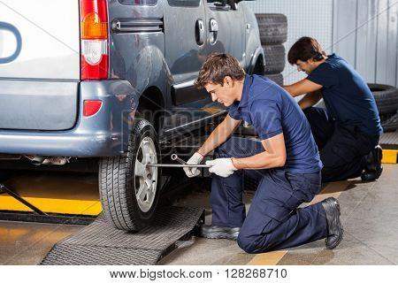 Male Mechanics Fixing Car Tires