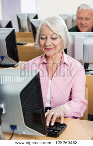 Senior Woman Using Desktop PC In Class