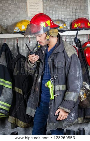 Firefighter Using Walkie Talkie In Fire Station