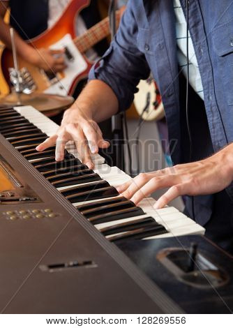 Band Member Playing Piano In Recording Studio