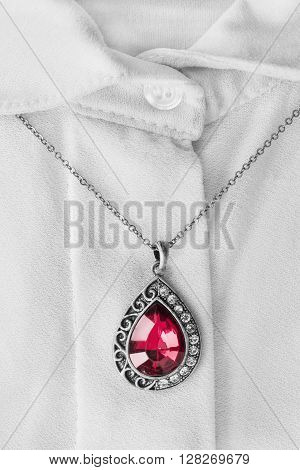 Red ruby pendant on white silk blouse closeup