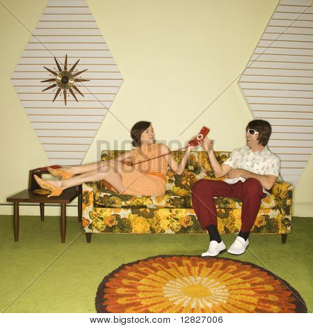 Caucasian mid-adult woman passing phone to Caucasian mid-adult man wearing sunglasses sitting on sofa.