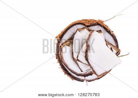 Overhead view of old brown organic coconut fruit copra broken into pieces and stacked on white background