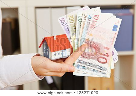 Hand holding house and Euro money as concept for real estate financing
