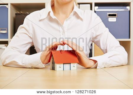 Hands of a business woman as roof protecting a small house