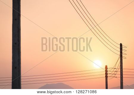The telegraph poles and wires in the sunset
