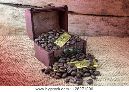 Old wooden chest with Coffee beans and Gold Bullion on Sackcloth background