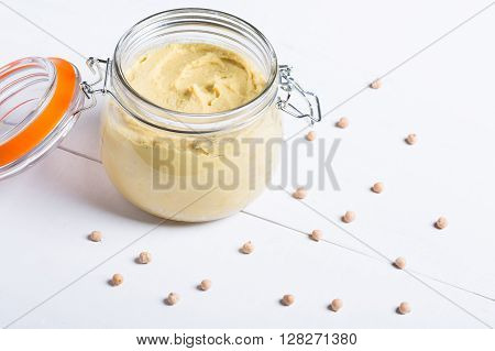 Homemade DIY natural vegan very healthy hummus of chickpeas in a glass jar on a wooden table