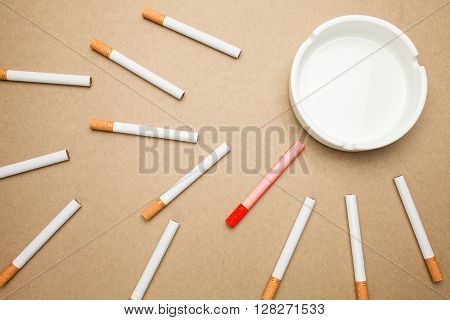 Business goal concept : cigarette and ashtray with brown background