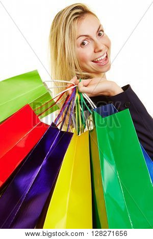 Happy young woman carrying many colored shopping bags