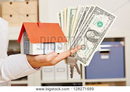 Hand of a woman holding small house with keys and Dollar money bills
