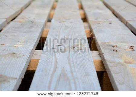 Photo of wooden bright brown planks with blurred foreground and background. Industrial pallet closeup. Shallow depth of field.