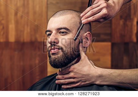 Portrait of young bald bearded man getting shaved with straight edge razor by hairdresser at barbershop on a wooden texture.