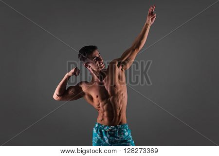 Muscle Man Posing In Studio, Gray Background, Bodybuilder Men's Physique In Blue Shorts