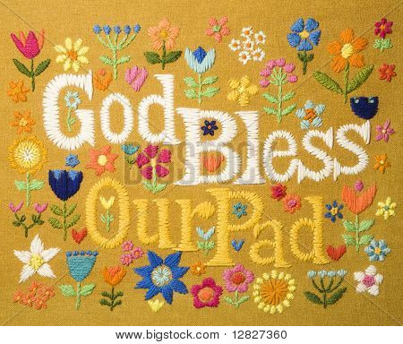 Vintage needlepoint wall hanging of colorful flowers surrounding the phrase God Bless Our Pad.