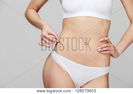Slim tanned woman's body Isolated over gray background
