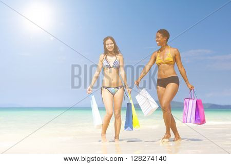 Women with shopping bags on a tropical beach.