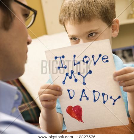 Caucasian boy giving mid adult father a drawing.