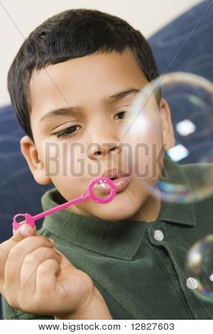 Hispanic boy blowing large soap bubbles.