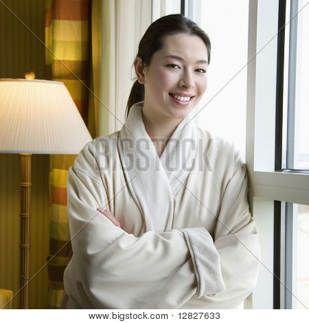 Taiwanese mid adult woman in bathrobe smiling at viewer with arms crossed.