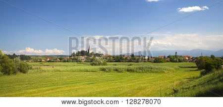 Idyllic rural view of gently rolling patchwork farmland and village in the summer