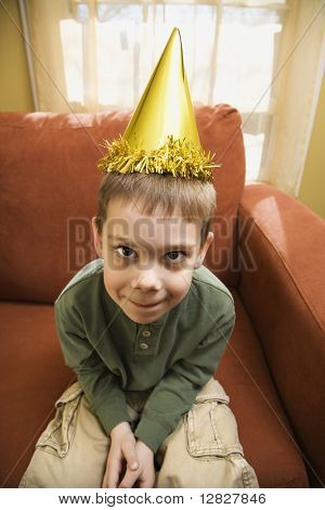 Caucasian boy with party hat looking at viewer and making facial expression.