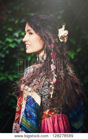 smiling young woman in boho style clothes and lot of hair accessories portrait in garden summer day