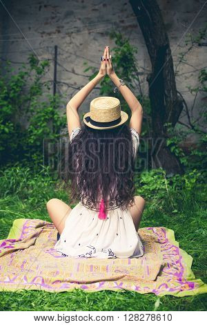 young woman in boho style clothes sit in garden back shot full body shot