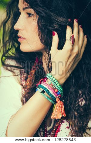young woman with lot of colorful  bracelets of beads focus on hand closeup