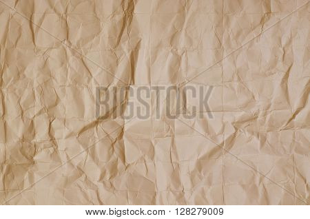 Close up of a creased, ocher  paper texture, full frame, horizontal