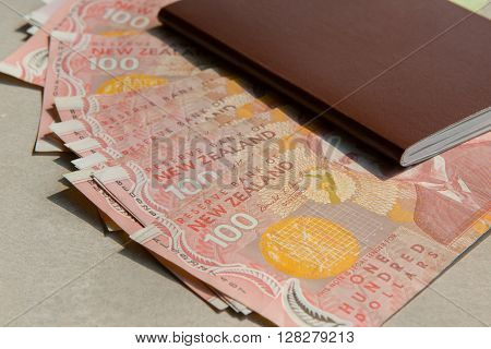stack of new zealand 100 dollars bank note and red cover personal passport book on cement floor