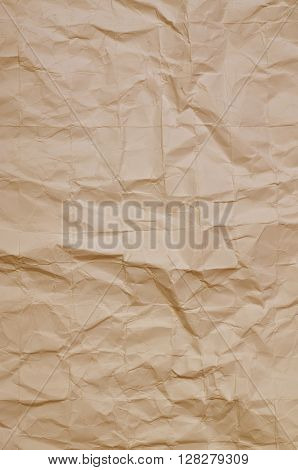 Close up of a creased, ocher  paper texture, full frame, vertical
