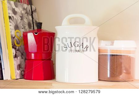 A bare wooden shelf on the wall with cooking notebooks and a red italian coffee machine along with one white ceramic pot of sugar and a pot of coffee