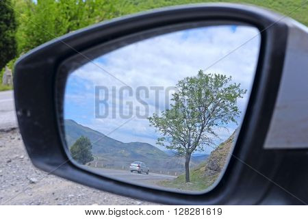 reflection of the mountain road in a car rear-view mirror