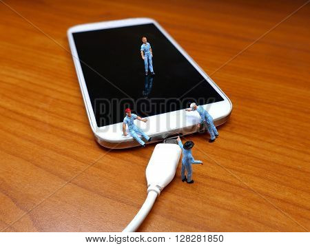 Miniature Workmen Inspecting Generic Cell Phone And Generic Charger Plug