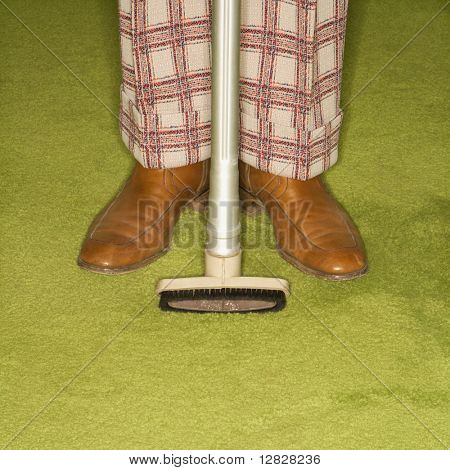 Close-up of Caucasian male legs in plaid pants with vacuum extension standing on green retro carpet.