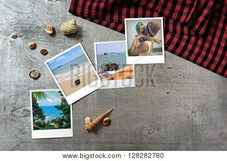 Beautiful seaside snapshots arranged on rustic wooden background with seashells and a scarf around horizontal top view with copy space
