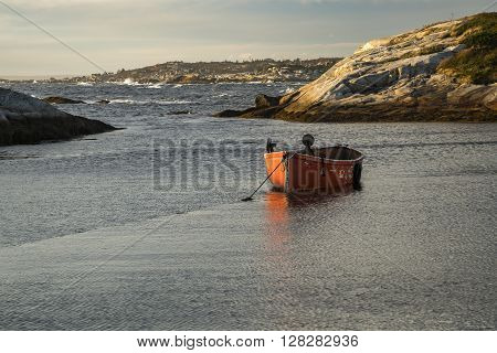 A small red fishing boat is anchored in the harbor at Peggy's Cove, Nova Scotia.