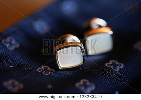 Closeup with elegant cufflinks on a blue tie