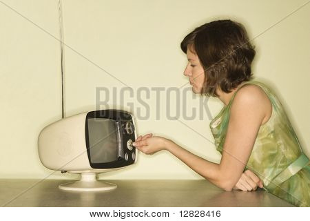 Side view of pretty Caucasian mid-adult woman sitting at 50's retro dinette set turning old televsion knob.