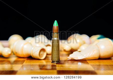 Closeup photo of one bullet standing on chessboard among lying chess pieces.