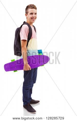 Full body Portrait of a school boy holding a skateboard and notebooks, isolated on white