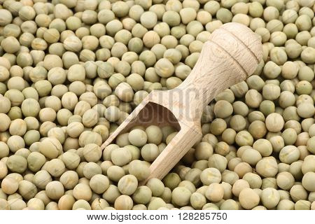 Green peas and wooden scoop background