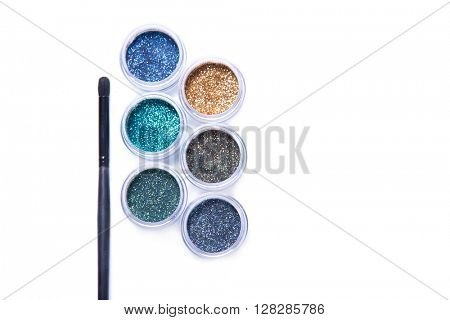 Makeup brush and colorful glitters in transparent jars, top view isolated on white background with copyspace