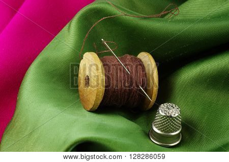 Wooden spool of thread with a needle and a thimble on a colored, creased fabrics.