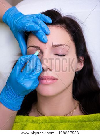 Cosmetician Preparing A Woman For Permanent Eyebrow Make Up
