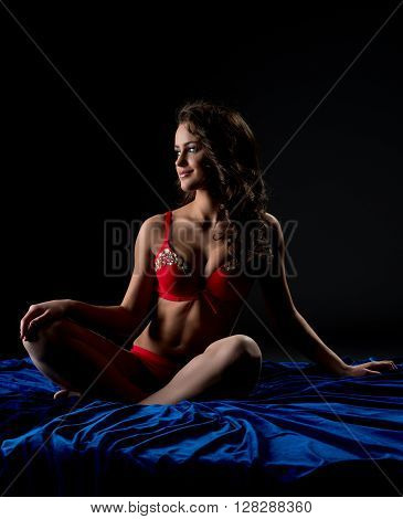 Image of pretty underwear model posing while sitting in bed