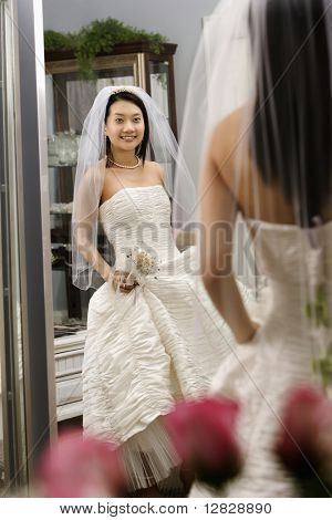 Asian bride admiring dress in mirror.