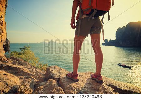 young woman hiker enjoy the view on sunset seaside