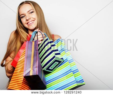 Beautiful young woman wearing red dress with shopping bags. Big sale.